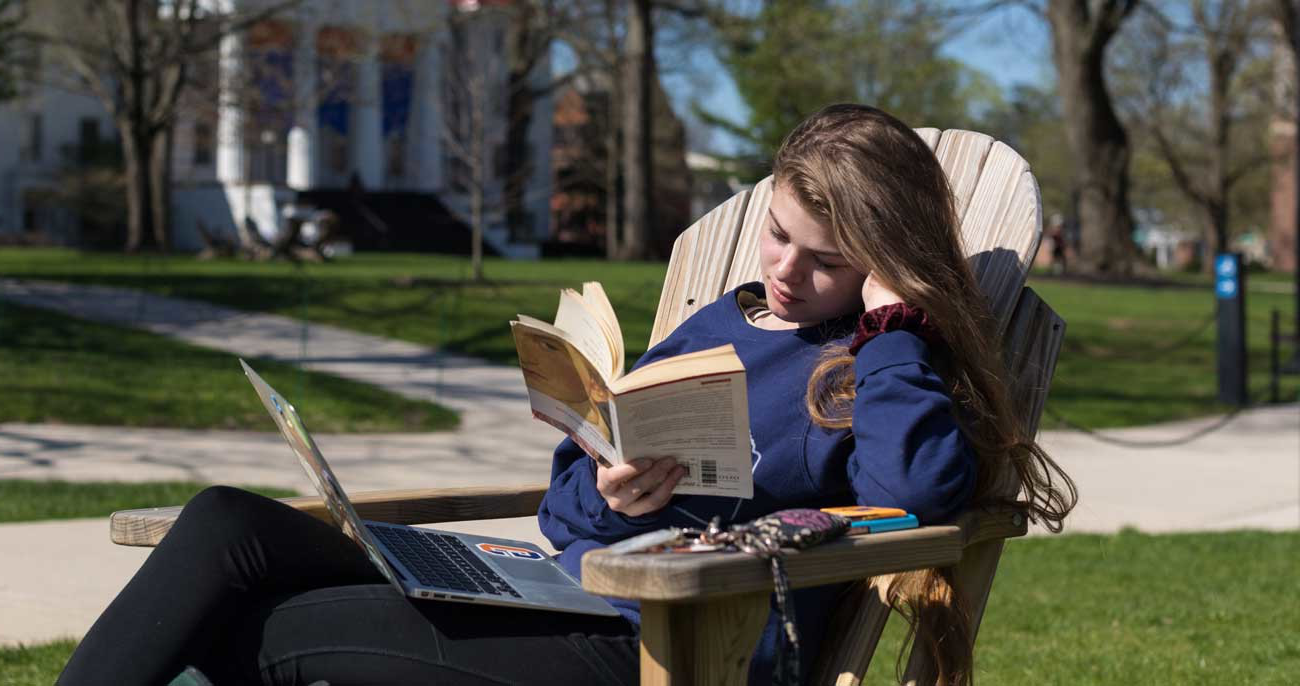 Student holding a book in an adirondack chair on Gettysburg College's campus